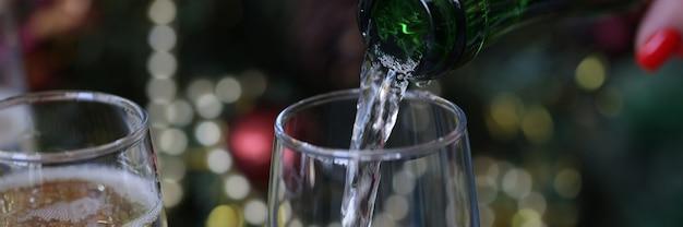 Mão feminina servindo champanhe da garrafa em copos para close-up de ano novo