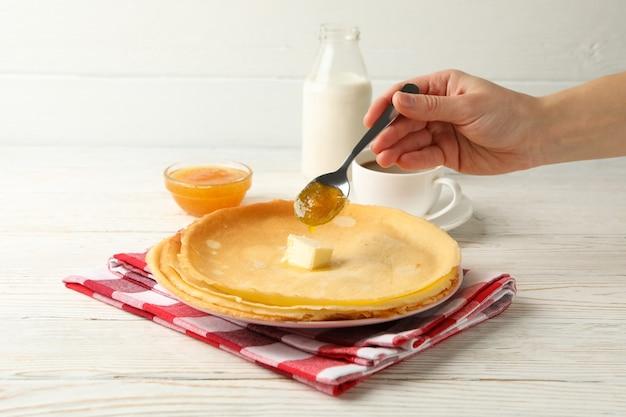 Mão feminina servindo geléia em rolos de crepe na mesa de madeira branca