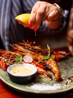 Mão feminina servindo limão sobre deliciosos camarões lagostins em restaurante