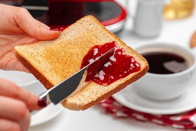 Mão feminina spresding geléia de morango em torrada assada