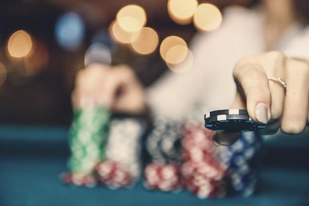 Mão feminina tirando fichas de pôquer da pilha