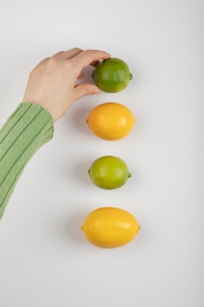 Mão feminina tirando limão de frutas cítricas em branco.