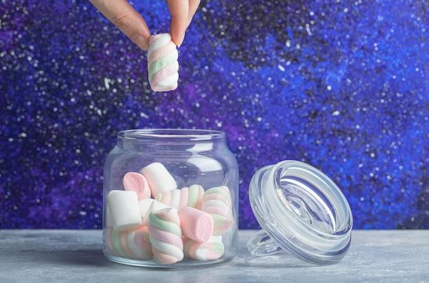 Mão feminina tirando marshmallows coloridos e macios de uma jarra de vidro