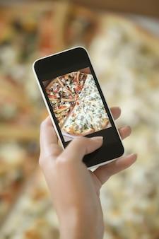 Mão feminina tirando uma foto de pizza