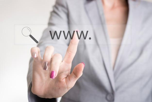 Mão feminina tocando uma barra de pesquisa da web com www e o ícone de lupa em uma tela virtual transparente.