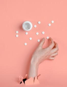Mão feminina toma pílula através de papel rosa rasgado. conceito de medicina criativa minimalista
