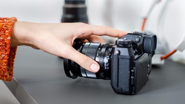 Mão feminina tomando uma câmera da mesa, microfone, lente da câmera e fones de ouvido perto dela. trabalhando em casa