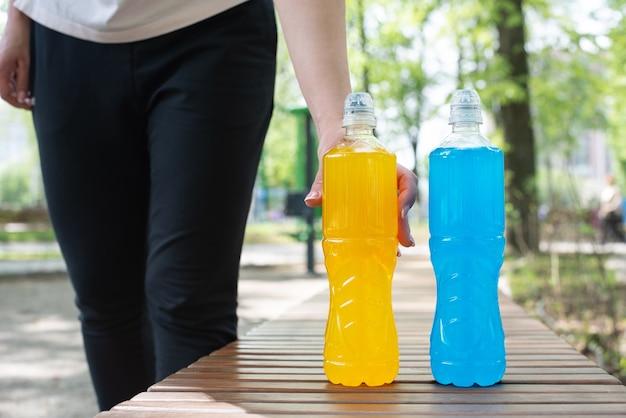 Mão feminina tomando uma garrafa de bebida isotônica durante uma pausa no treinamento para a restauração do equilíbrio água-sal na rua, verão, close-up.