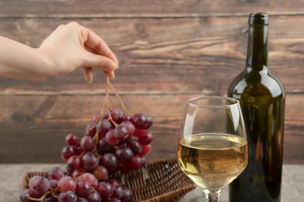 Mão feminina tomando uvas vermelhas da cesta de vime.