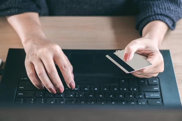 Mão feminina usando cartão de crédito compras on-line
