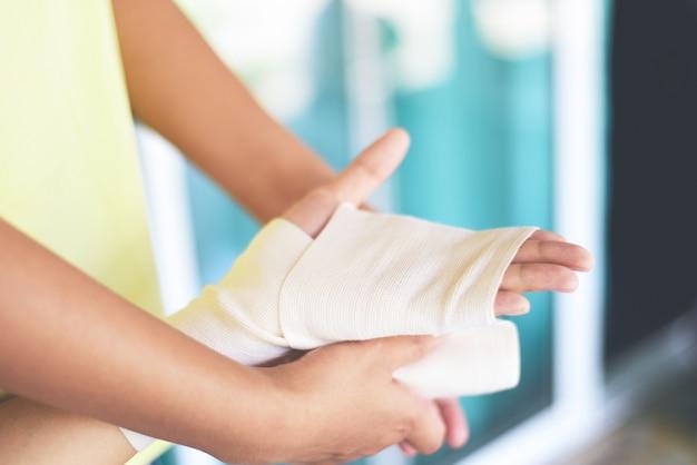 Mão ferida bandagem braço pela enfermeira - cuidados de saúde de lesão de pulso de primeiros socorros e conceito de medicina
