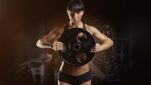 Mão forte de mulher muscular fitness bombeamento músculos com placa