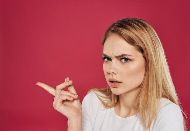 Mão gesticulando o dedo indicador feliz loira modelo vermelho plano de fundo. foto de alta qualidade