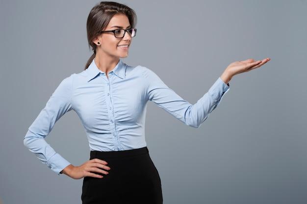 Mão gesticulando por uma mulher vestida formal
