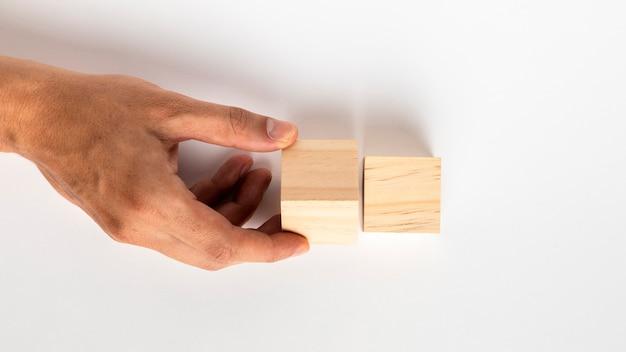 Mão girando pequeno cubo de madeira