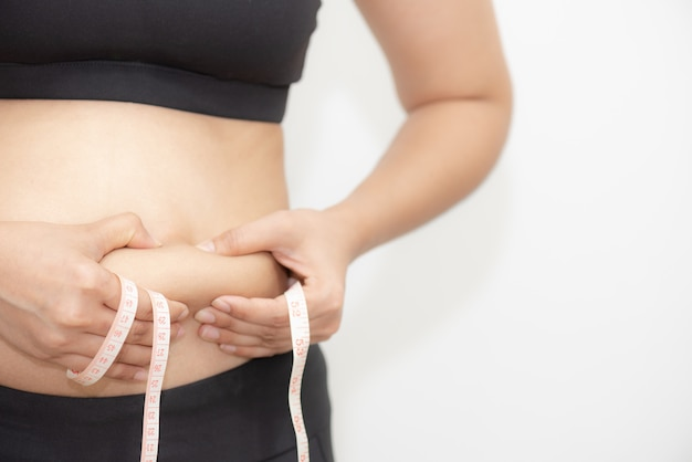 Mão gorda da mulher que mantém a barriga excessiva gorda com fita de medição no fundo branco.