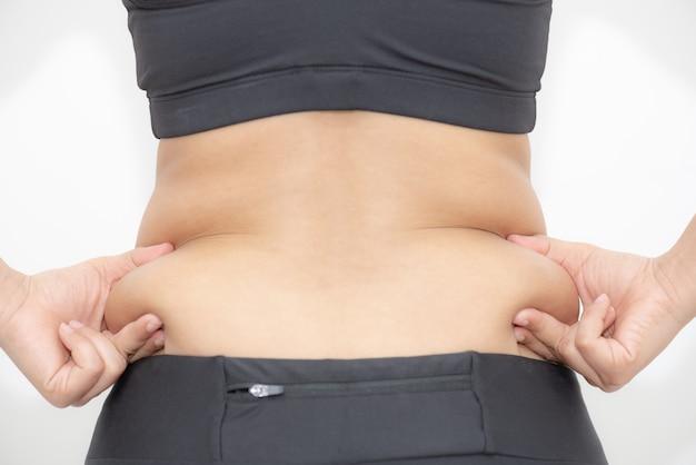 Mão gorda da mulher que mantém a barriga excessiva gorda no fundo branco.