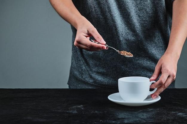Mão holdong colher cheia de café no preto.
