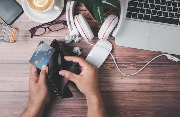 Mão homem abrir carteira vazia e segurando o cartão de crédito na mesa de escritório de madeira