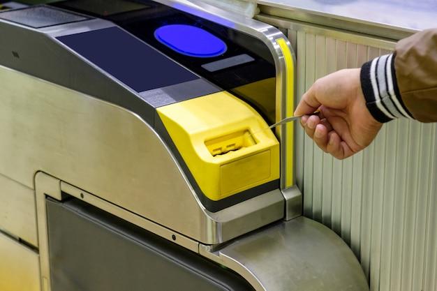Mão homem, inserindo, bilhete, cartão metrô, em, entrada