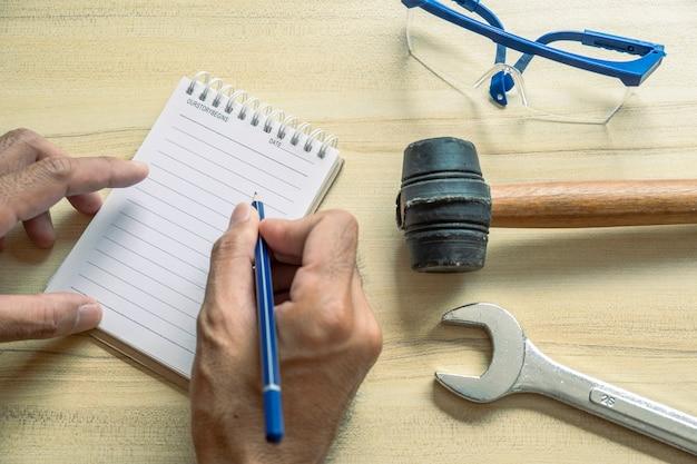 Mão homem pessoas com bloco de notas para verificação de fábrica ou indústria na mesa para inspetor de escrita de notas.