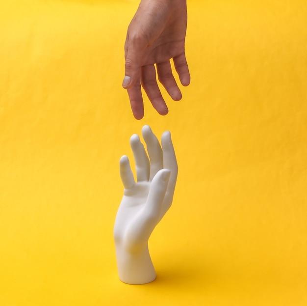 Mão humana alcançando a mão do manequim em um fundo amarelo. minimalismo