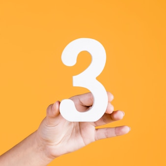 Mão humana, atrasando, a, numere 3, contra, um, amarela, fundo