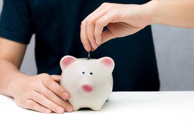 Mão humana colocando moedas em um cofrinho. salvando o conceito.