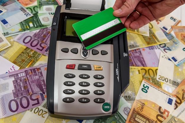 Mão humana com cartão de crédito e terminal com notas de euro