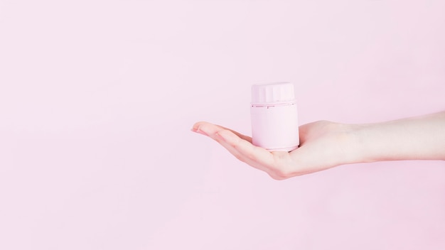 Mão humana com garrafa para comprimidos de medicamento sobre fundo rosa
