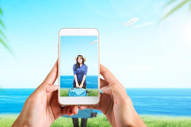 Mão humana com o celular tirando foto de mulher asiática viajando com uma mala no campo com fundo de paisagem marinha
