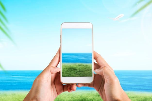 Mão humana com o celular tirando uma foto em campo com fundo de paisagem marinha