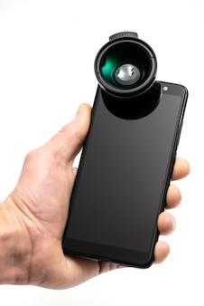 Mão humana com smartphone e lente.