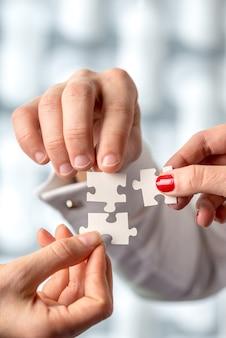 Mão humana conceitual, segurando as peças do quebra-cabeça