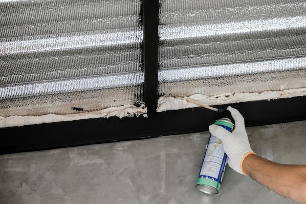 Mão humana em luva branca está vedando vazamentos de telhado com espuma de calafetar enlatada.
