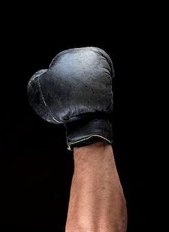 Mão humana em luva de boxe de couro preto levantada