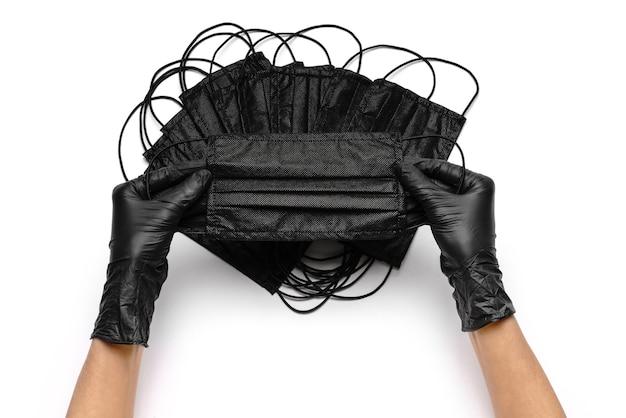 Mão humana em luva de proteção segurando máscaras de proteção facial