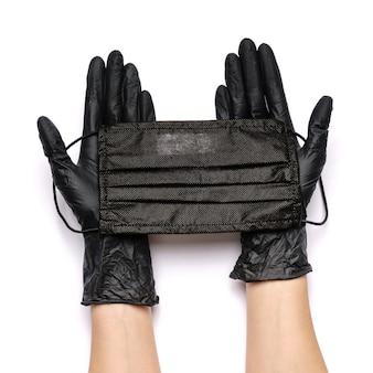Mão humana em luva protetora segurando máscaras protetoras de rosto isoladas no fundo branco.