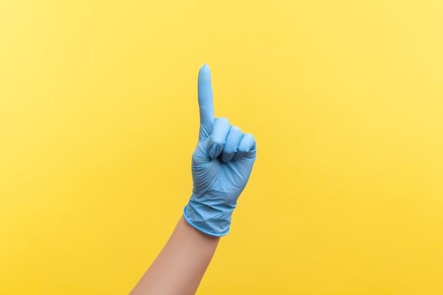 Mão humana em luvas cirúrgicas azuis mostrando o número um com o dedo ou aparecendo com o lado
