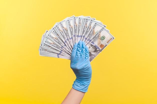 Mão humana em luvas cirúrgicas azuis segurando e mostrando leque de dinheiro do dólar americano na mão.