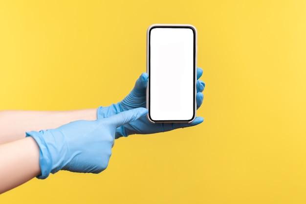 Mão humana em luvas cirúrgicas azuis segurando e mostrando o telefone inteligente e apontando para o visor vazio.