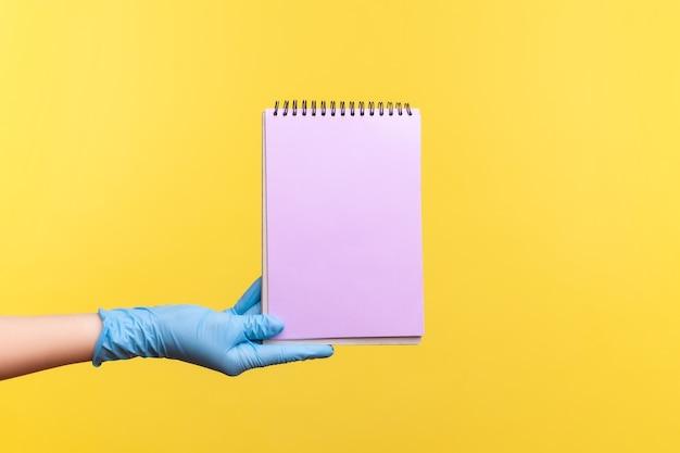 Mão humana em luvas cirúrgicas azuis, segurando o bloco de notas roxo na mão e segurando um papel vazio.