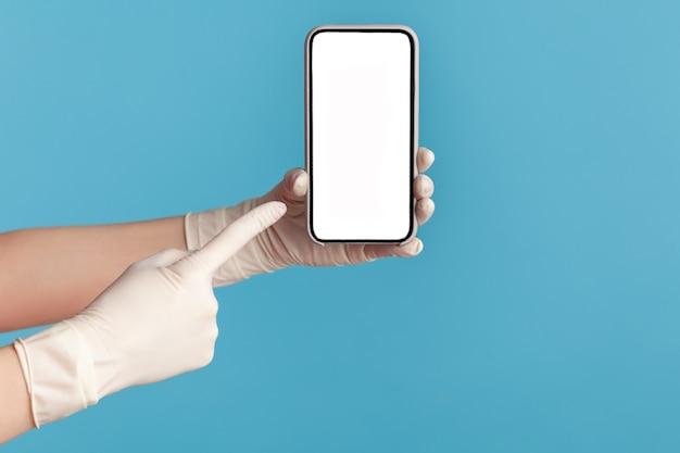 Mão humana em luvas cirúrgicas brancas segurando e mostrando o telefone inteligente e apontando para o visor vazio.