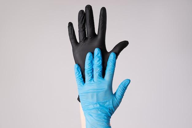 Mão humana em luvas de látex na parede cinza, surto de doença coronavírus 2019 ou covid-19