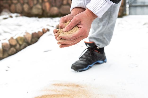 Mão humana espalhando areia em estradas com neve