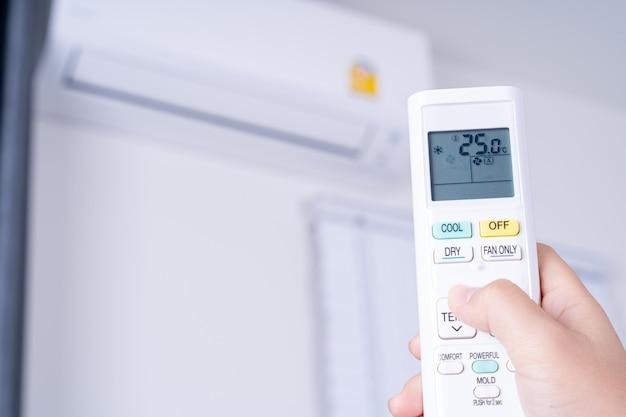 Mão humana está usando o controle remoto branco do ar condicionado