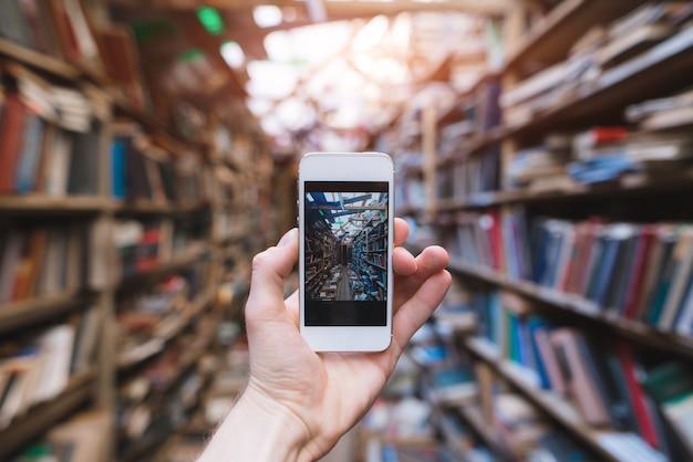 Mão humana faz uma fotografia de uma biblioteca pública em uma câmera do smartphone.