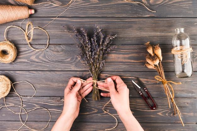 Mão humana fazendo buquê de flores usando corda perto de garrafa de vidro sobre a mesa texturizada