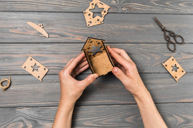 Mão humana fazendo casa de papelão na mesa de madeira