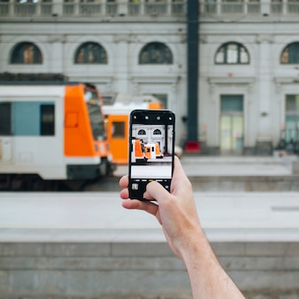 Mão humana, fazendo exame retrato, de, trem estrada ferro, com, cellphone